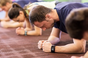 man with heart-rate tracker exercising in gym